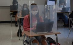 Navigating her laptop in Geometry class, Kylie Madura, freshman, completes her school work. Classes have taken on a new look this school year, with plastic dividers, masks and new furniture in general.