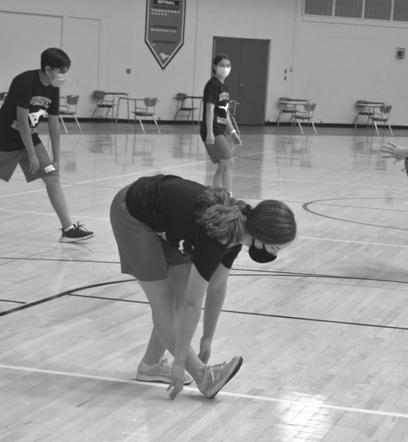 Adorned in her mask, Emma Jez, freshman, stretches during her physical education class.