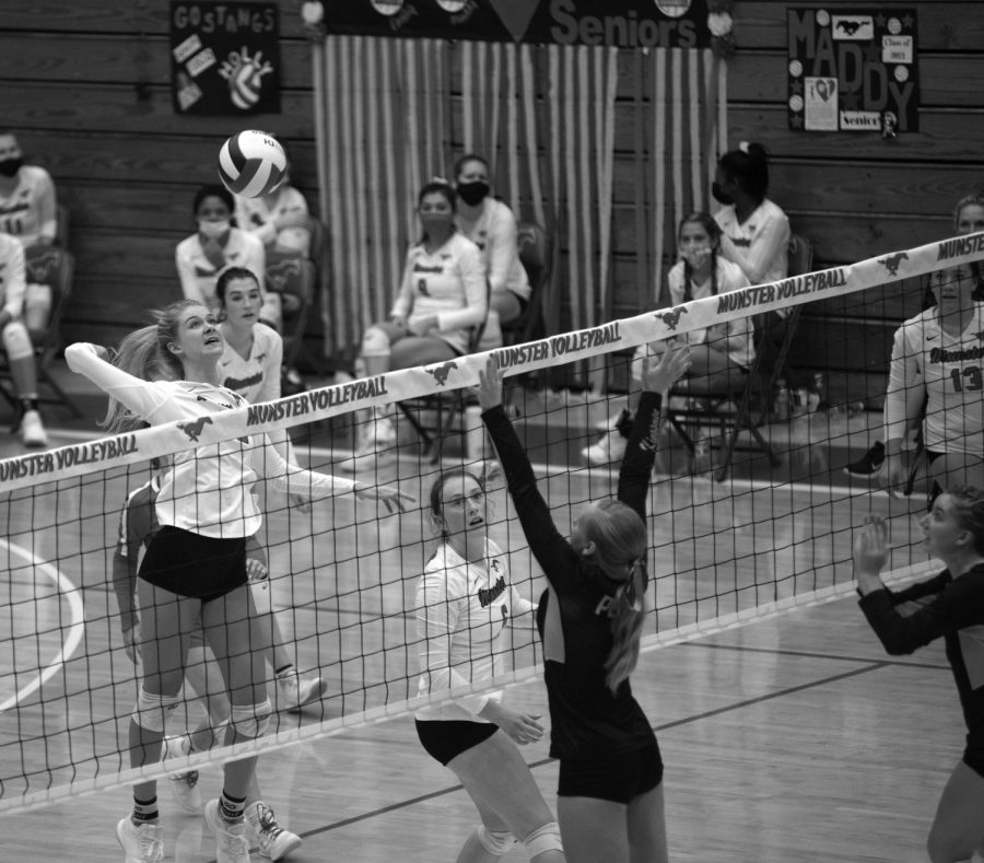 "OVER THE NET At the game last weekend against Penn, Emily Banaszek, senior, jumps to hit a slide set and get the kill. The girls celebrated the point and the three set victory over Penn. Regionals are at LaPorte High School this Saturday. ""I knew I had to get around the block to be able to get the kill, so I took the opportunity when I saw it,"" she said."