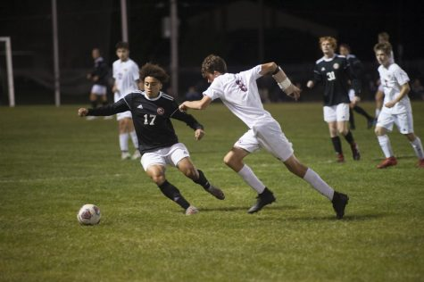 """DRIBBLE AND DODGE In a soccer match against Lowell on Sept. 23, Ethan Orange, senior, dodges, dribbles and circumvents around the defender. Boys' Soccer won the game with a final score of 8-0. Boys' Soccer sectionals will be held at Highland High School on Monday Oct. 5, and they currently maintain a record of 4-2-1, """"I scanned the field to look for my teammates to set them up to score,"""" Ethan said."""