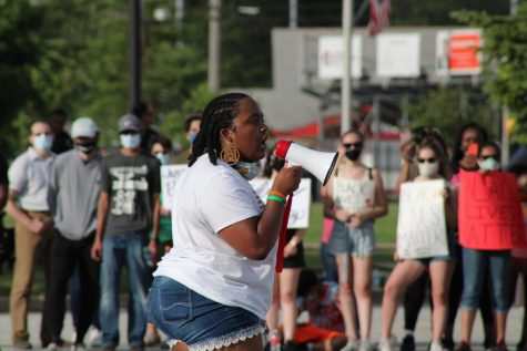 "NO JUSTICE NO PEACE Speaking on a megaphone to a listening crowd, Kayla Prowell, class of '19, recites a poem during the protest that occurred June 5. Kayla also later helped plan a second protest at the town hall. Munster saw a surge of students, graduates and adult support in response to the resurgence of Black Lives Matter this year, paralleling the peaceful protests that have been sparked throughout the nation, ""We're tired of having to do this. We're tired of having to fight for our rights over and over and over again. We fought for them 300 years ago, we fought for them 100 years ago, we fought for them 60 and 50 years ago. We're always fighting, and I think that we're tired of being our own advocates. We're tired of people not being tired of being racist."""