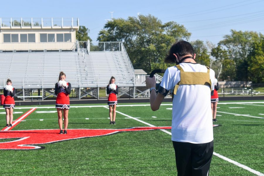 "THREE, TWO, ONE, ACTION In order to prepare for the Homecoming virtual pep rally, Francis Hovland, senior, films the cheer routine. Film club, established this year by Francis and Sarah Resch, senior, have been in charge of assembling a video for the school to stream in place of an in-person rally. ""We hope it'll be among the best of our projects,"" Francis said."