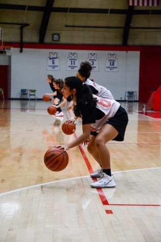 "DRIBBLE IT, PASS IT: At their practice on Dec. 3, Mia Unzueta, freshman, runs dribbling drills with her teammates. Having a few bumps in the road due to Covid-19, ""With a couple of girls being ill, we all work together as a team and fight through it,"" she said."