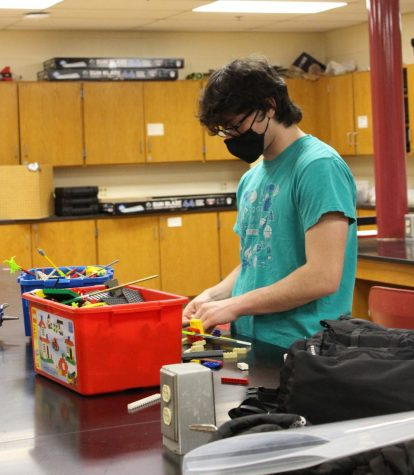 """MODELING ASSISTANCE Making a model, Jacob Katz, junior, helps his teammates work on an event at practice. Jacob would create the model and hand it to another person for them to rebuild it. """"I build with legos because they hold a lot of possibilities,"""" Jacob said."""