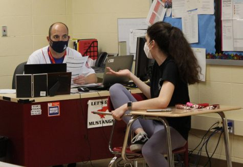 "Discussing with DECA member Amelia Konstantinopoulos, junior, Mr. Ryan Popa, business teacher, helps prepare for the upcoming International Career Development Conference (ICDC). The ICDC is an internats competition that consists of a roleplay event and a written event. ""The competition is incredibly strong,"" he said, ""but we have a good chance of having some teams qualify for Finals which would take place next."""