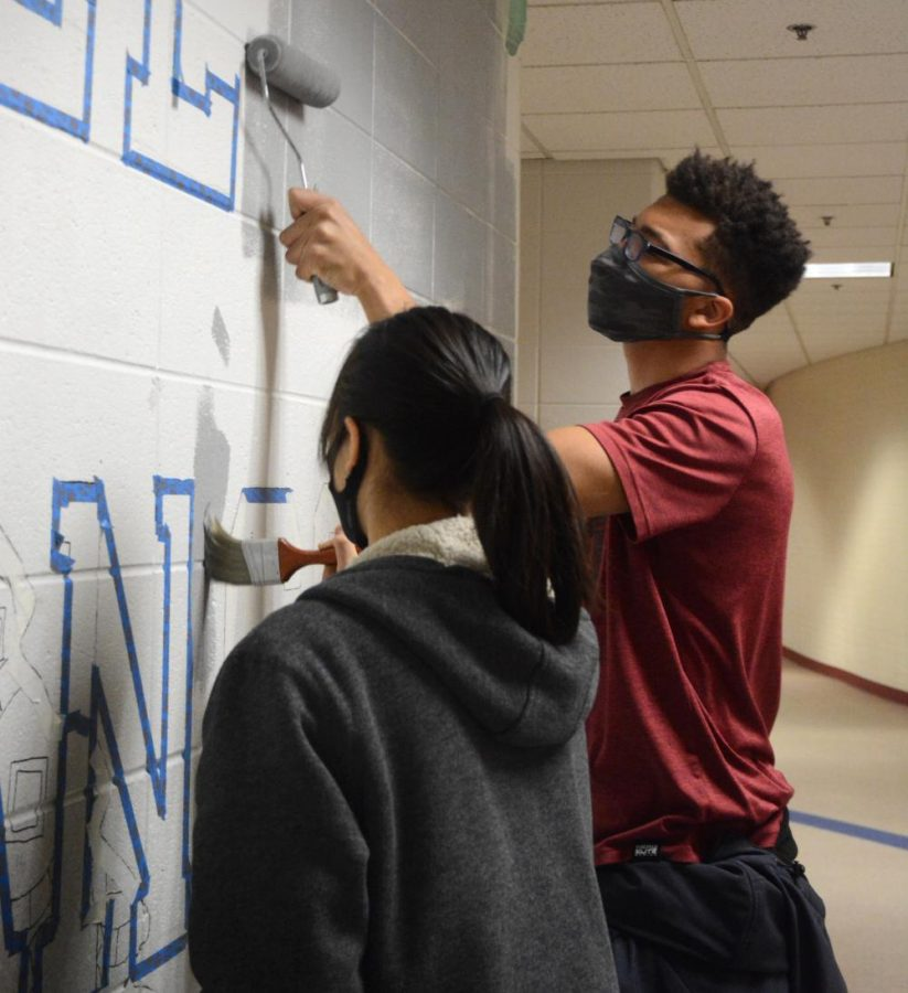 The completion of the three year-old mural continues it's progress as Nhi Nguyen, junior, and Carmani Shedrich, senior begin to paint the background.