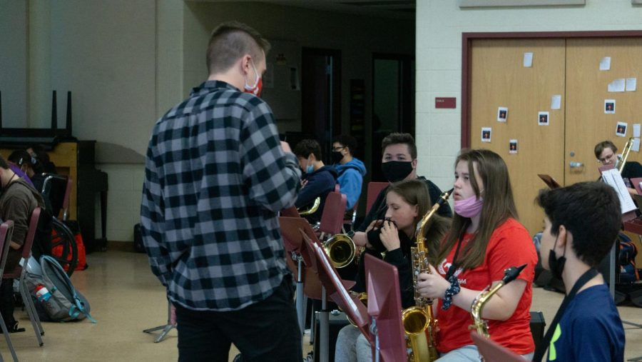 STAYING IN TUNE instructing Concert Band, Ian Marcusiu, Assistant Band Director, teaches Payton Wujek, freshman, how to play a segment for their upcoming concert on May 22 It is very important for a performance based class like band to have performance opportunities, he said.
