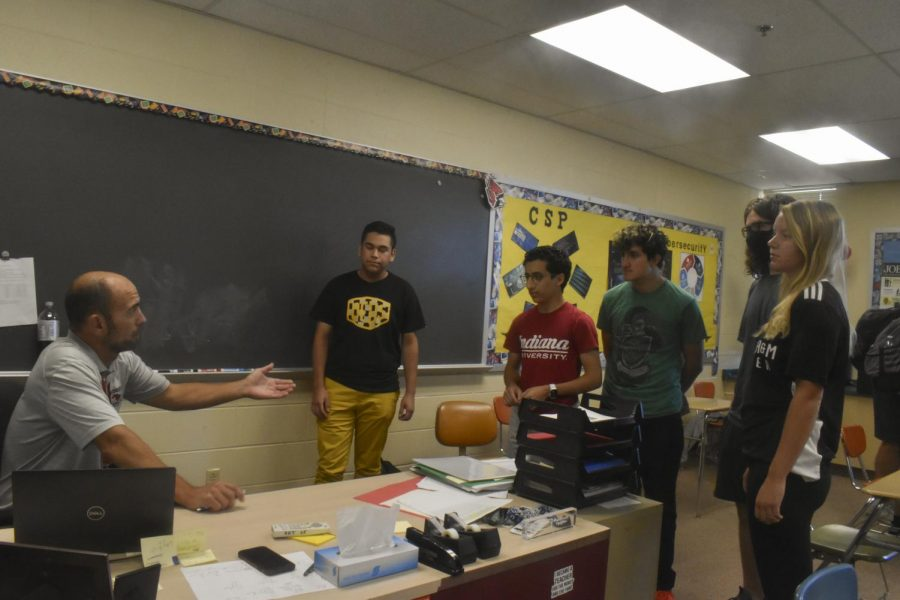 BEGINNING AN ERA CybersPatriot club members discuss upcoming competitions and plans with Mr. Popa,business teacher and the club's sponsor.