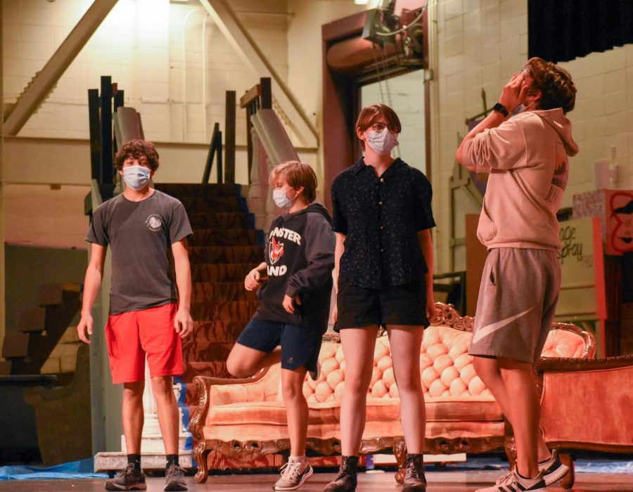 """LOOSENING UP Dancing, running, jumping and stretching, Joey Hladek, sophomore, freshmen Charlie Ilijevski and Evvy Kikkert, and James Ferguson, junior, warm up on stage before beginning rehearsal. Theatre warms up as a group to prepare both their minds and bodies to get into character. """"We just run through different acts (and) then we have a little powwow at the end,"""" James said."""