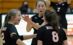 """WICKED WIN Celebrating after scoring a point, seniors Emma Miles, Marina Gronkiewicz and Grace Clark, win their game against Hobart on Sept. 9. """"Despite even the score, I felt confident in us and knew we were going to pull through,"""" Marina Gronkiewicz, senior, said."""