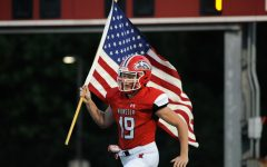 """RAISING THE FLAG As the crowd roars, Thomas Choros, senior, carries the American flag in front of the team. Football was ecstatic to play at home against Hanover Central on Aug. 27. """"The boys were all buzzing and were ready to hit,"""" Choros said. """"Personally, I was ready to run through a wall."""""""