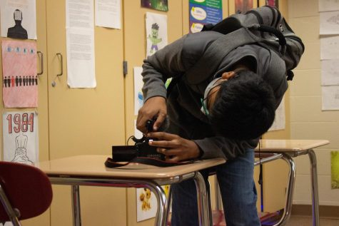 EVERYTHING IN FOCUS Adjusting his camera settings, Alex Mohammed, freshman, gets ready for Film Club.